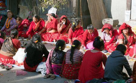 hinduist: KATHMANDU, NEPAL, 16TH OF DECEMBER 2013 - Hinduist woman sitting and eating alongside of hinduist temple in Kathmandu city Editorial