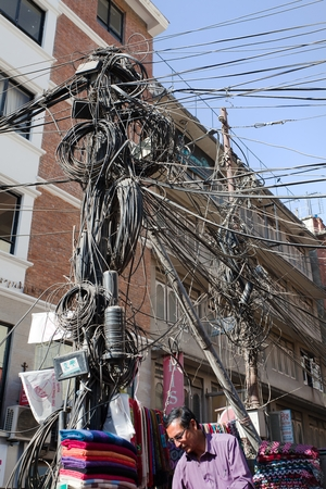 nepali: KATHMANDU, NEPAL, 16TH OF DECEMBER 2013 - dangerous power line and vendor with Kashmir fabric