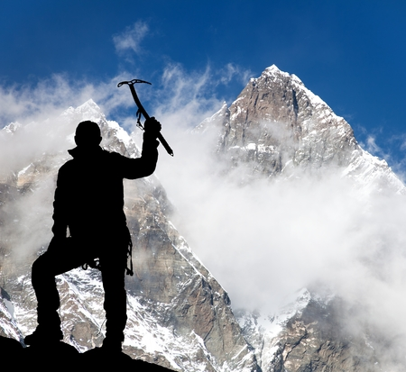 ice axe: Mount Lhotse and silhouette of man wirh ice axe - trek to everest base camp - Nepal Stock Photo