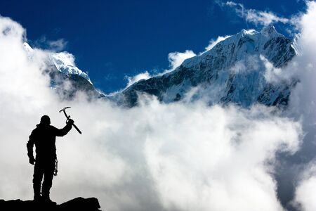 ice axe: Silhouette of man with ice axe in hand and mountains with clouds - Mount Thamserku and Mount Kangtega - Nepal