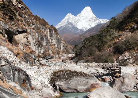 VIew of mount Ama Dablam with stony and wooden bridge above river - way to everest base camp - Khumbu valley - Nepal photo