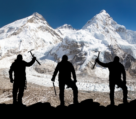 alpinist: Silhouette of men with ice axe in hand, Mount Everest and Lhotse from Pumo Ri base camp - way to Everest base camp - Nepal
