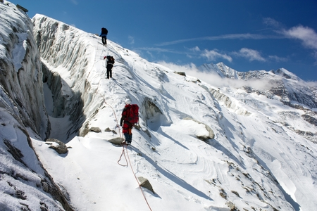 everest: group of climbers on rope on glacier - sunny day on mountain Stock Photo