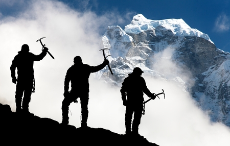 ice axe: Silhouette of men with ice axe in hand and mountains with clouds  Mount Thamserku and Mount Kangtega  Nepal