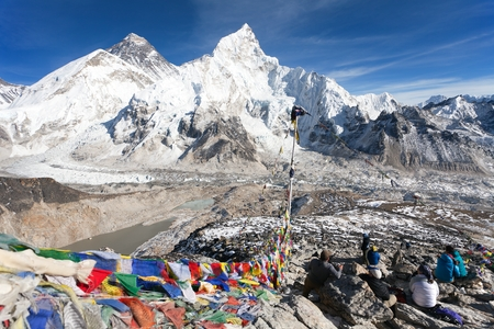 View of Mt. Everest Lhotse and Nuptse with prayer flags and tourists from Kala Patthar view point near Gorak Shep and Everest base camp Khumbu valley Sagarmatha national park Nepal