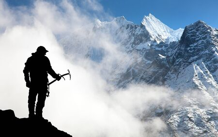ice axe: Silhouette of man with ice axe in hand and mountains with clouds  Mount Thamserku and Mount Kangtega  Nepal