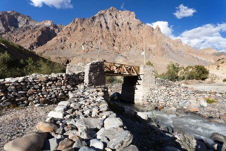 indian creek: woody and stone bridge with prayer flags on Zanskar trek, Ladakh, jammu and Kashmir, India
