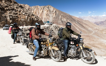 enfield: KHARDUNG LA PASS, LADAKH, INDIA, 11th SEPTEMBER 2013 - motocycles brand Royal Enfield and biker in highest road pass on the world Khardung La, Ladakh, Jammu and Kashmir, India