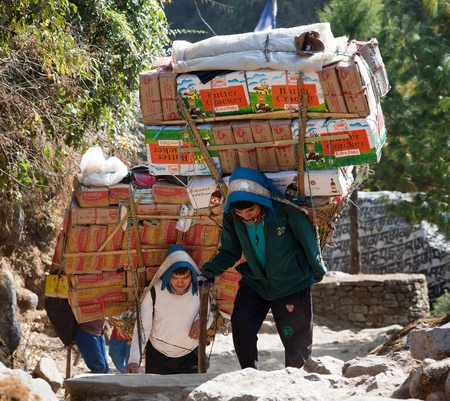 sherpa: KHUMBU, NEPAL, 1st DECEMBER 2014 - Sherpa porters with goods going from Lukla to Namche Bazar, way to Everest base camp, Khumbu valley, Sagarmatha national park, Nepal Editorial