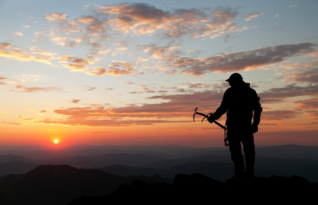 ice axe: Evening silhouette - view of man on mountains with ice axe in hand