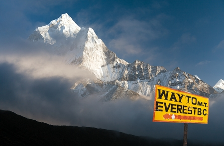 signpost way to mount everest b.c. and evening himalayan panorama with mount Ama Dablam