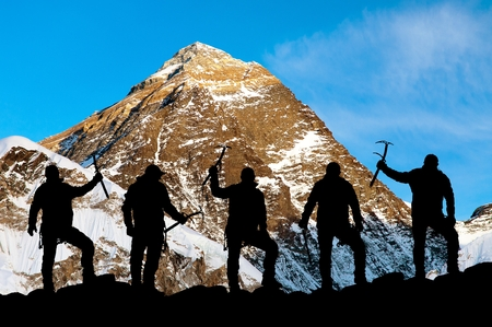 ice axe: Evening view of Mount Everest and silhouette of climbers with ice axe in hand, extreme sport in Nepal, Khumbu valley, Solukhumbu, trek to Everest base camp, Sagarmatha national park Stock Photo