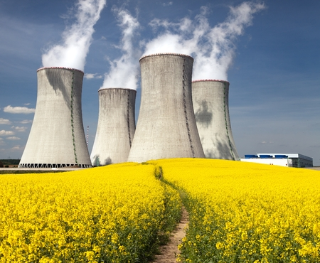dukovany: Nuclear power plant Dukovany with golden flowering field of rapeseed - Czech Republic - two possibility for production of energy Stock Photo