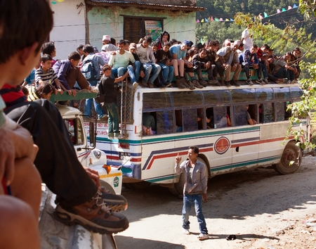 omnibus: LANGTANG AREA, NEPAL, 20th OCTOBER 2010 - people traveling on top of autobus brand TATA in Nepalese Himalayan mountain road