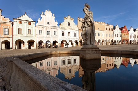 mirroring: TELC, CZECH REPUBLIC, 28TH AUGUST 2015 - Evening view of Telc or Teltsch town square, building mirroring in public fountain with statue of st. Margaret, Czech republic. World heritage site by unesco Editorial