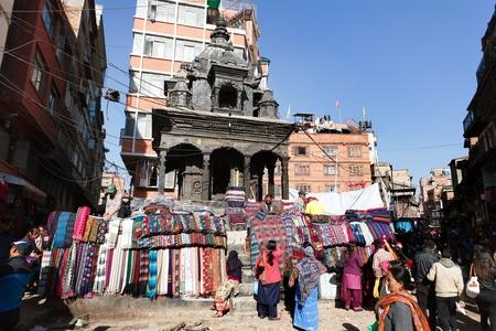 hinduist: KATHMANDU, NEPAL, 16th DECEMBER 2013 - street seller of pashmina, kashmir and yak wool tectile and hindu temple Editorial