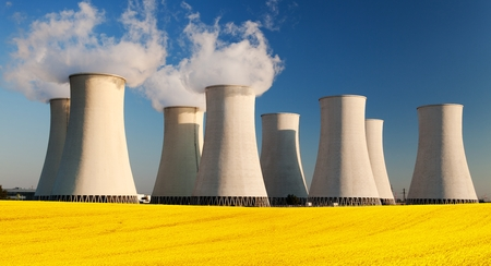 flowering field: Panoramic view of Nuclear power plant Jaslovske Bohunice with golden flowering field of rapeseed - Slovakia - two possibility for production of electric energy