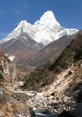 brooks camp: View of mount Ama Dablam with stony and wooden bridge above river - way to everest base camp - Khumbu valley - Nepal