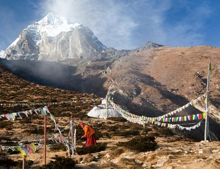 lamaism: KHUMBU VALLEY, NEPAL - 8th NOVEMBER 2014 - Buddhist monk, stupa and prayer flags near Pangboche monastery and Tabuche peak, life in Khumbu valley on the way to Everest base camp Editorial