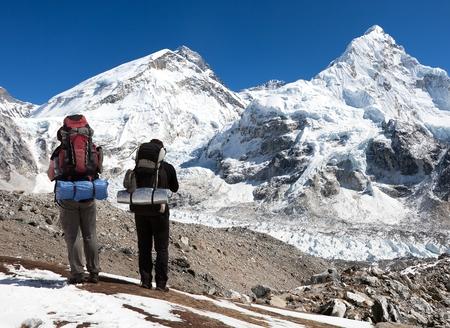 highlander: vista del Monte Everest, Lhotse y Nuptse del campo base Pumo Ri con dos turistas en el camino hacia el campamento base, el Parque Nacional de Sagarmatha, valle de Khumbu - Nepal Foto de archivo
