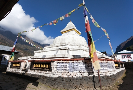 Stupa with prayer flags and wheels on the way from Lukla to Namche bazar in chaurikharka near chheplung village - nepal