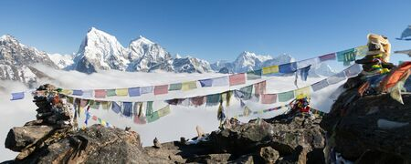 sierra: view from Gokyo Ri to Arakam Tse, Cholatse, Tabuche Peak, Thamserku and Kangtega with prayer flags - trek to Everest base camp - Nepal