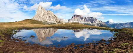 ra: View from passo Giau to mount Ra Gusela from Nuvolau gruppe and Tofana or Le Tofane Gruppe with clouds, mountain mirroring in lake, Dolomites, Italy