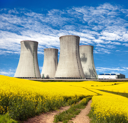 plant nature: Nuclear power plant Dukovany with golden glowering field of rapeseed and rural road - Czech Republic - two possibility for production of energy Stock Photo