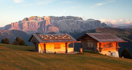 Evening view of two small cabin and Sella Gruppe or Gruppo di Sella, South Tirol, Italian dolomities mountains, Italy Stock Photo