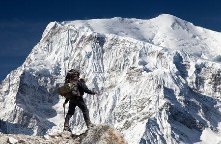View of south rock face of mount Annapurna 3 III, Annapurna range and hiker, Annapurna circuit trekking trail, Nepal Stock Photo