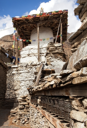 stupa one: Stupa and prayer wheels wall in Manang villlage, one of the best villages in round Annapurna circuit trekking trail route, Nepal Stock Photo