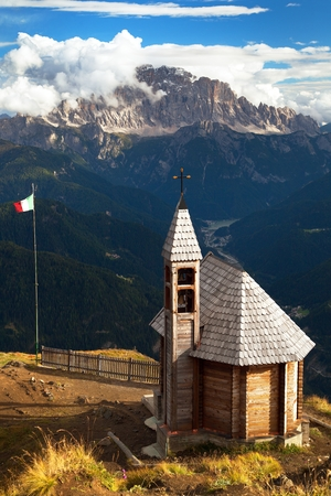 Small wooden church or chapel on the mountain top Col di Lana and Mount Civetta, Alps Dolomites mountains, Italy