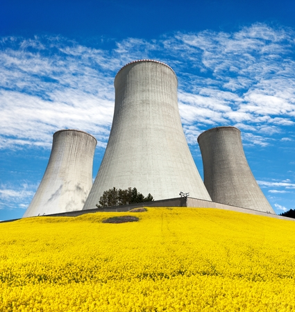 Nuclear power plant Dukovany, cooling tower with golden flowering field of rapeseed, canola or colza- Czech Republic - two possibility for production of energy