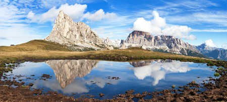 le: View from passo Giau to mount Ra Gusela from Nuvolau gruppe and Tofana or Le Tofane Gruppe with clouds, mountain mirroring in lake, Dolomites, Italy