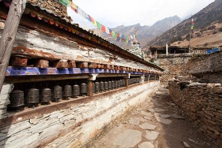 Buddhist prayer many wall with prayer wheels in nepalese village, round Annapurna circuit trekking trail, Nepal