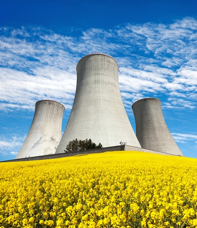 dukovany: Nuclear power plant Dukovany, cooling tower with golden flowering field of rapeseed, canola or colza- Czech Republic - two possibility for production of energy