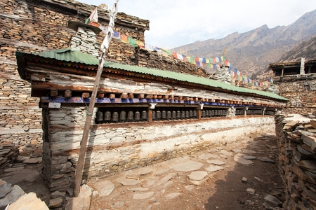 sanskrit: Buddhist prayer many wall with prayer wheels in nepalese village, round Annapurna circuit trekking trail, Nepal