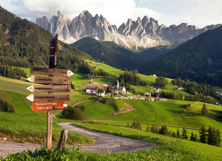 evening panoramic view of Geislergruppe or Gruppo dele Odle from Saint Magdalena with tourist sign post, Italian Dolomites Alps mountains