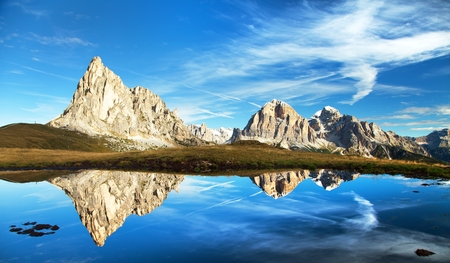 mirroring: View from passo Giau to mount Ra Gusela from Nuvolau gruppe and Tofana or Le Tofane Gruppe with clouds, mountain mirroring in lake, Dolomites, Italy