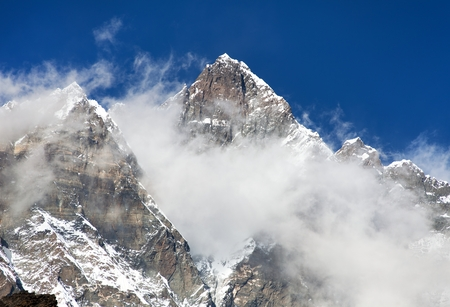 Top of Lhotse with clouds on the top - way to mount Everest base camp, Khumbu valley, Sagarmatha national park, Nepalese Himalayas Stock Photo