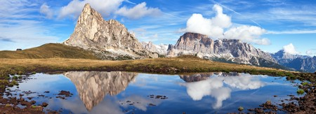 View from passo Giau to mount Ra Gusela from Nuvolau gruppe and Tofana or Le Tofane Gruppe with clouds, mountain mirroring in lake, Dolomites, Italy