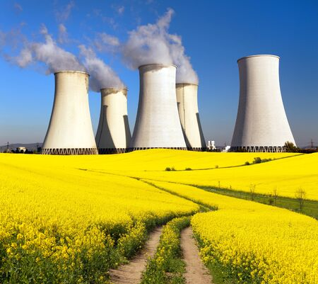Panoramic view of Nuclear power plant  with golden flowering field of rapeseed, canola or colza - Slovakia - two possibility for production of electric energy Stock Photo