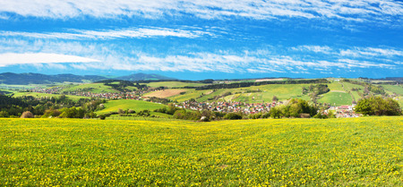 panoramic view of Horni Lidec village with meadow ful of dandelions and beautiful clouds - Carpathiam mountains - Czech Republic Stock Photo