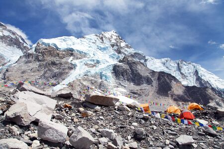 view from Everest base camp to west rock face of Nuptse peak with tents and prayer flags, Sagarmatha national park, nepal, Himalayas