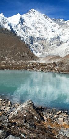 view of mount Cho Oyu mirroring in lake - Cho Oyu base camp - Everest trek - Nepal Himalayas mountains