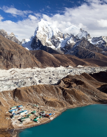 Gokyo lake or Dudh Pokhari Tso and village, Ngozumba glacier, Arakam tse peak and chola tse from Gokyo Ri - trek to Cho Oyu base camp, Khumbu valley, Sagarmatha national park, Nepal Himalayas mountain Stock Photo