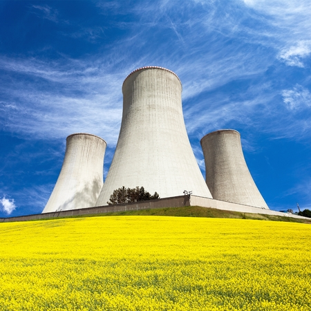 Nuclear power plant Dukovany, cooling tower with golden flowering field of rapeseed, canola or colza- Czech Republic - two possibility for production of energy 版權商用圖片 - 117079656
