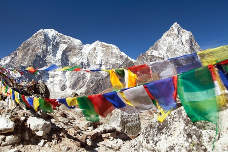 Rows of prayer flags and mounts Arakam Tse and Tabuche peak, Sagarmatha national park, trek to Everest base camp, Khumbu valley, Solukhumbu - Nepal Himalayas mountains Stock Photo