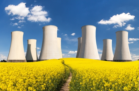 Nuclear power plant Jaslovske Bohunice cooling towers with golden flowering field of rapeseed, canola or colza, Slovakia, two possibility for production of electric energy, panoramis view