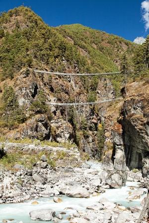 Two rope hanging suspension bridges in Nepal Himalayas under Namche Bazar above Dudh Koshi Nadi river, Mount Everest base camp trek Stock Photo - 124963256
